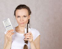 Young lady has a glass of water and pilss Stock Photography
