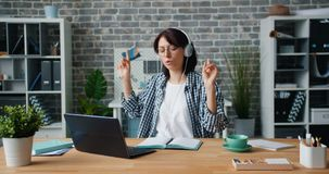 Young lady in headphones enjoying music working with laptop in office at work. Young lady in headphones is enjoying music working with laptop in office at work stock video footage