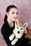 Young Lady With Her Cute Akita Puppy. Portrait of young happy woman with little cute akita dog stock image