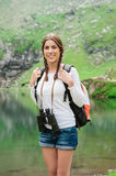 Young lady hiker with backpack sitting on mountain. Young caucasian female hiker holding binoculars. Vertical shape. Glacial Lake on Transfagarasan road, Fagaras stock photos