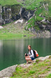 Young lady hiker with backpack sitting on mountain. Young caucasian female hiker holding binoculars. Vertical shape. Glacial Lake on Transfagarasan road, Fagaras royalty free stock photography