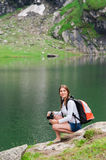 Young lady hiker with backpack sitting on mountain Stock Photos