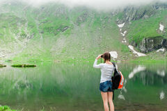 Young lady hiker with backpack sitting on mountain. Young caucasian female hiker watching through binoculars. Glacial Lake on Transfagarasan road, Fagaras stock images