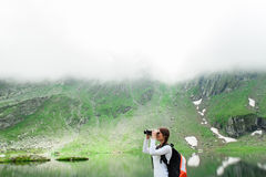 Young lady hiker with backpack sitting on mountain. Young caucasian female hiker watching through binoculars. Glacial Lake on Transfagarasan road, Fagaras royalty free stock photography
