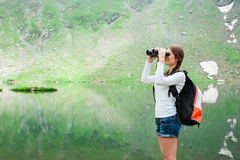 Young lady hiker with backpack sitting on mountain Royalty Free Stock Photos