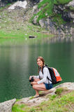 Young lady hiker with backpack sitting on mountain. Young woman admiring the beautiful view of the lake and mountains, holding a binocular. Scene from Balea Lake stock photo