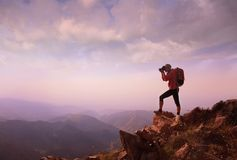 Young woman hiker taking photo on mountain peak stock photography