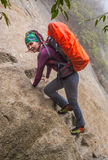 Young lady hiker with backpack walking in mountains royalty free stock image