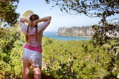 Young lady hiker with hair braids enjoying view of tropical beach from top of a mountain. Sea, jungles and rocks around.  royalty free stock images