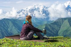 Young lady hiker preparing something to eat in the mountains Stock Photography