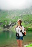 Young lady hiker. Scene from Balea Lake, Romania. Young caucasian female hiker holding binoculars. Vertical shape. Glacial Lake on Transfagarasan road, Fagaras stock photo