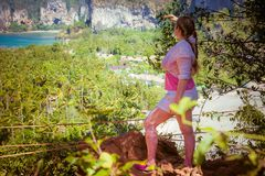 Young lady hiker in white and pink clothes with hair braids Looks into the distance and enjoying view of tropical beach from top. Of a mountain stock photo