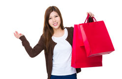 Young lady hold with shopping bag and hand present something Royalty Free Stock Image