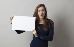 Young lady holding blank board or paper for a commercial Stock Photos
