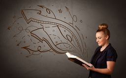 Young lady holding book with arrows Stock Image