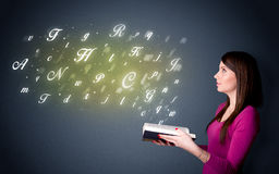 Young lady holding book with letters Stock Images