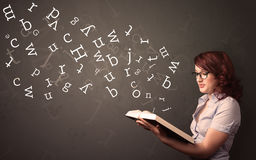 Young lady holding book with letters Stock Photos