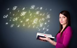 Young lady holding book with letters Royalty Free Stock Image