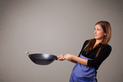 Young lady holding a frying pan Stock Images