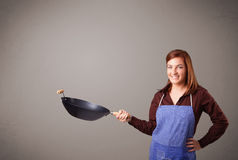 Young lady holding a frying pan Royalty Free Stock Photography