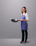 Young lady holding a frying pan Stock Image