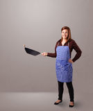 Young lady holding a frying pan Royalty Free Stock Photos