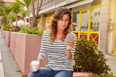 Young lady holding a hot drink while using mobile Stock Photography