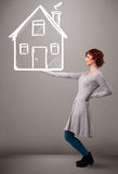 Young lady holding a huge drawn house Stock Photography