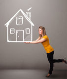 Young lady holding a huge drawn house Royalty Free Stock Images