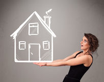 Young lady holding a huge drawn house Stock Image