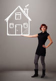 Young lady holding a huge drawn house Royalty Free Stock Photos