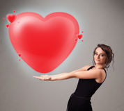 Young lady holding lovely 3d red heart Stock Images
