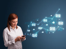 Young lady holding a phone with arrows and message icons Royalty Free Stock Photography