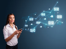 Young lady holding a phone with arrows and message icons Royalty Free Stock Image