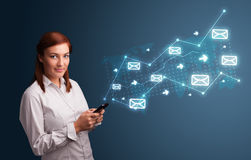 Young lady holding a phone with arrows and message icons. Attractive young lady standing and holding a phone with arrows and message icons Royalty Free Stock Photo