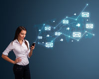 Young lady holding a phone with arrows and message icons Stock Photography