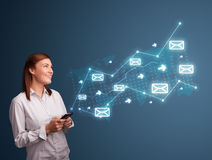 Young lady holding a phone with arrows and message icons Stock Photos