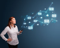 Young lady holding a phone with arrows and message icons. Attractive young lady standing and holding a phone with arrows and message icons Stock Photo