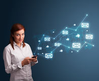 Young lady holding a phone with arrows and message icons Stock Images