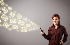 Young lady holding a phone with message icons Royalty Free Stock Photos
