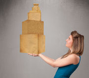 Young lady holding a set of brown cardboard boxes Stock Photos
