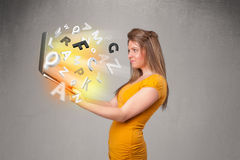 Young lady hoolding notebook with colorful abstract letters Stock Image