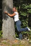 Young lady hugging tree. Young lady ugging tree with one foot in the air Stock Photos