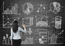 Free Young Lady Is Drawing Some Charts And Graphs On The Black Chalkboard. Rear View Of The Model. Stock Image - 59272111