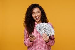 Young lady isolated over blue background. Looking camera showing display of mobile phone holding money. Portrait of an excited young african isolated over yellow stock photos