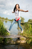 Young lady jumping by the lake Stock Image