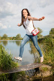 Young lady jumping by the lake Royalty Free Stock Photography