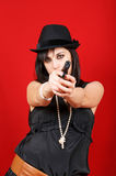Young lady killer. Portrait of a young woman wearing a black hat and pointing a gun to the camera. Studio shot over red background Royalty Free Stock Image