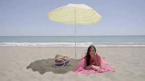 Young lady laying down on beach blanket. Single cute young lady laying down on beach blanket next to bag in shade under yellow umbrella with ocean in background stock video footage