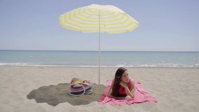 Young lady laying down on beach blanket. Single cute young lady laying down on beach blanket next to bag in shade under yellow umbrella with ocean in background stock footage